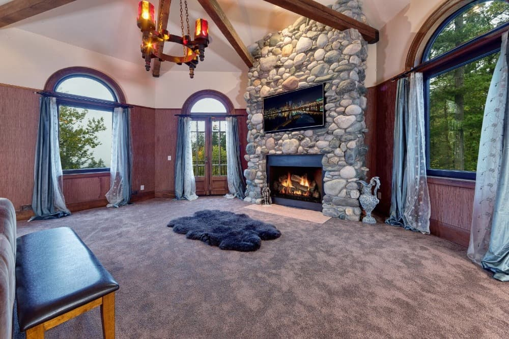 Another one of the living spaces with a large stone fireplace with a widescreen TV on it. Images courtesy of Toptenrealestatedeals.com.