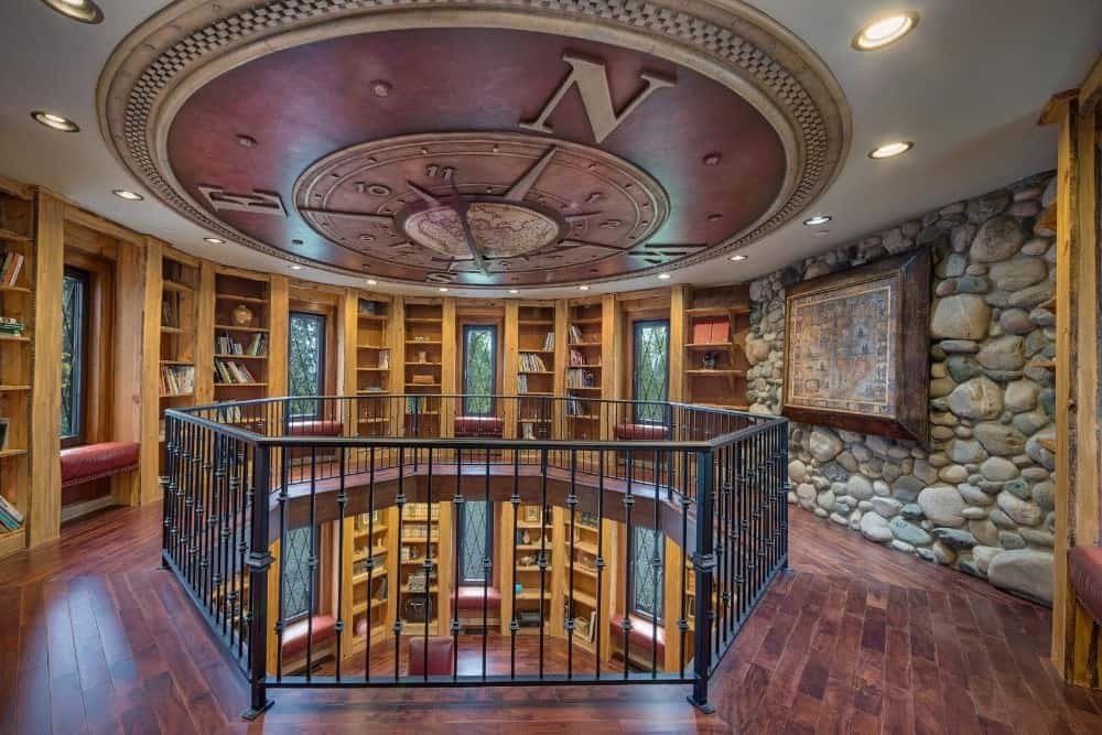 The house also has a large library with a personal office desk setup. The area is a two-story and has a stunning clock-designed ceiling. Images courtesy of Toptenrealestatedeals.com.
