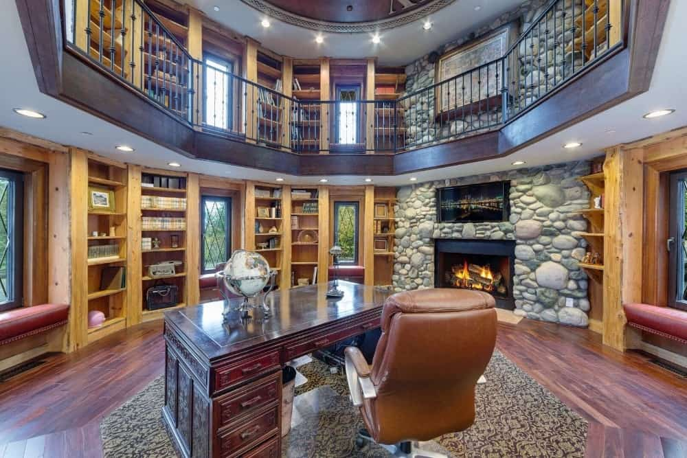 The library boasts a two-story area with multiple bookshelves and has a personal office desk. There are a widescreen TV and a stone fireplace as well. Images courtesy of Toptenrealestatedeals.com.