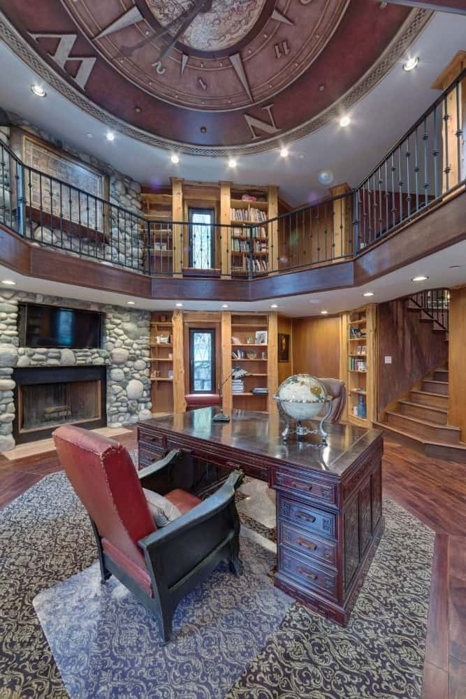 Another look at the library showcasing its personal office desk surrounded by multiple bookshelves. Images courtesy of Toptenrealestatedeals.com.