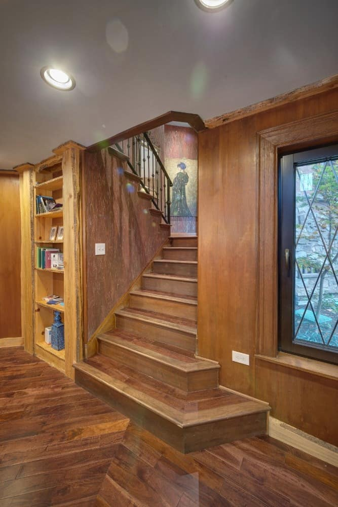 This staircase leads to the library's second floor. There's a built-in bookshelf on the side as well. Images courtesy of Toptenrealestatedeals.com.
