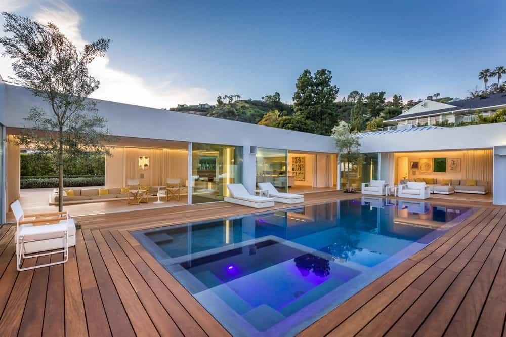 The beautiful home that has a zero-edge pool and spa in the backyard surrounded by wooden walkways that leads to the various large open walls of the home glowing yellow from the interior lights. Images courtesy of Toptenrealestatedeals.com.