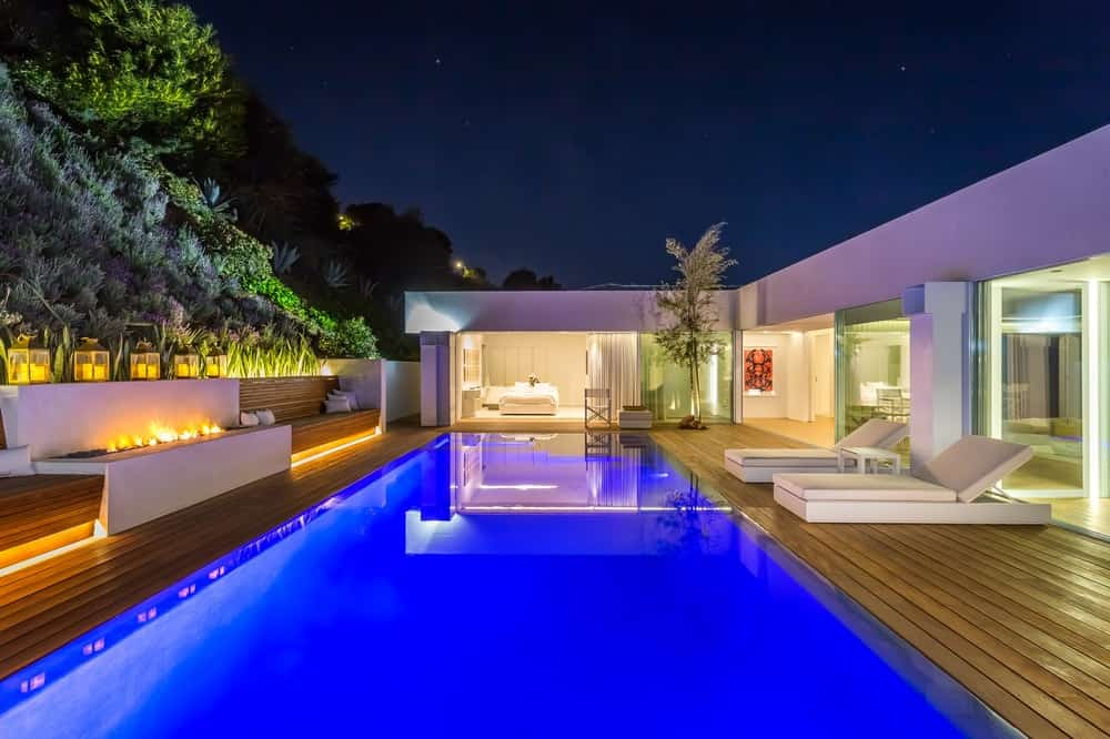 At night, the built-in lights of the pool and the surrounding landscaping come alive bringing with it an ethereal scene that presents a calming scenery. Images courtesy of Toptenrealestatedeals.com.