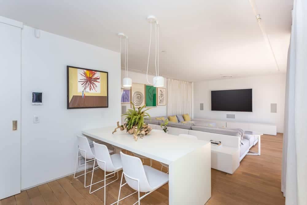 The home also has an informal dining area that also serves as a breakfast bar with a waterfall white structure paired with three white modern chairs adorned with a centerpiece and a colorful wall-mounted artwork on the white wall. Images courtesy of Toptenrealestatedeals.com.