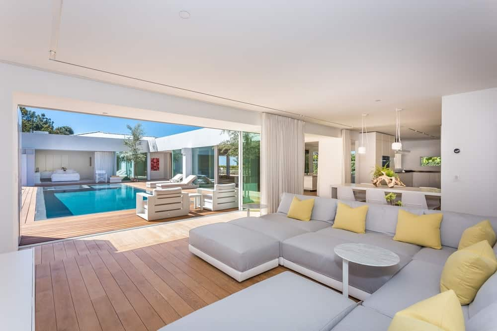 Right beside the informal dining area is the family room with a large sectional gray sofa facing a large wall-mounted TV and a clear view of the backyard pool. Images courtesy of Toptenrealestatedeals.com.