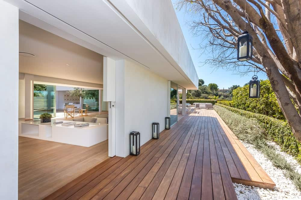 The walkway to the main entryway is made of wooden slats that is lined on one side by outdoor lamps. Across from this is the tall shrubs walling in the property. Images courtesy of Toptenrealestatedeals.com.