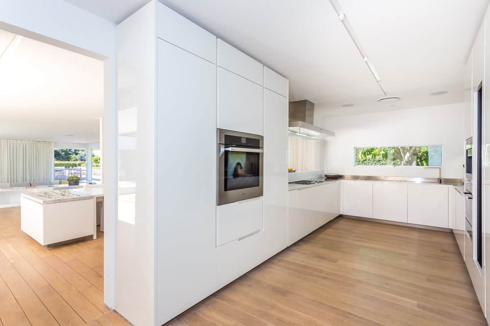 The modern kitchen has a wide hardwood flooring surrounded by a U-shaped cabinetry and counter lining the walls with the same white and slick look as the rest of the house. Images courtesy of Toptenrealestatedeals.com.