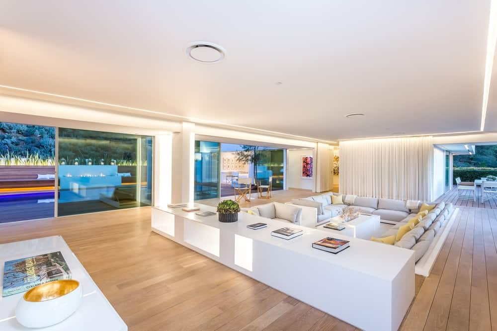 From the foyer area, the sunken living room conversation pit is visible bordered by a low white wooden structure serving as a large console table. and display surface. Images courtesy of Toptenrealestatedeals.com.