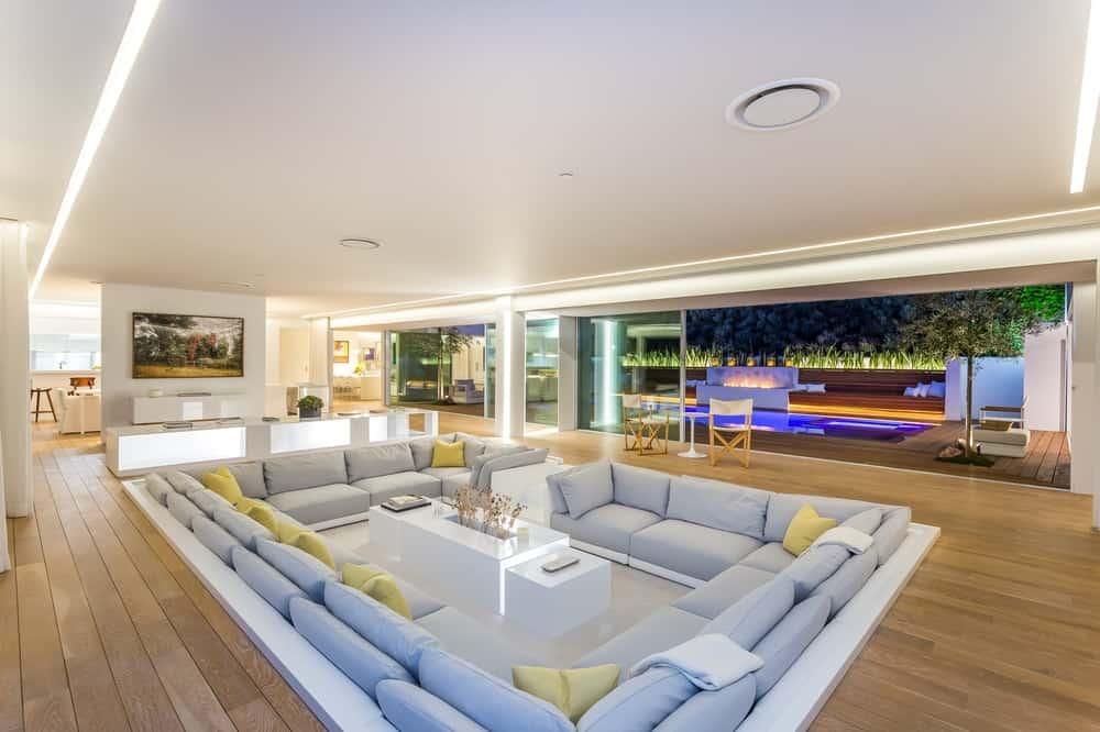 A closer look at the sunken living room conversation pit shows that a central white modern coffee table in the middle is surrounded by built in light gray cushioned seats accented with a few green pillows. Images courtesy of Toptenrealestatedeals.com.