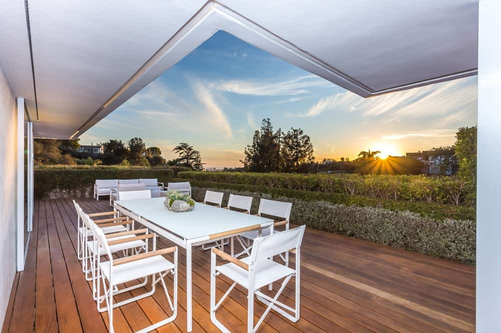Just outside of the large sliding glass walls is a charming outdoor dining area with an awesome view of the sunset through treetops. Images courtesy of Toptenrealestatedeals.com.