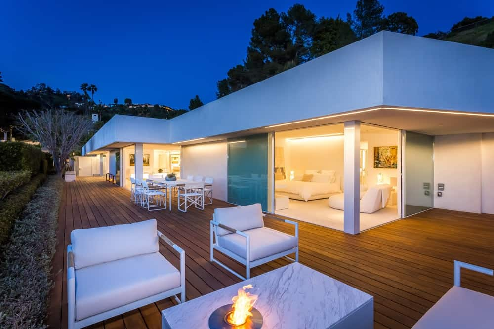 A few steps from the outdoor dining area is an outdoor patio with a modern firepit surrounded by cushioned arm chairs that stand out against the wooden walkways. Images courtesy of Toptenrealestatedeals.com.