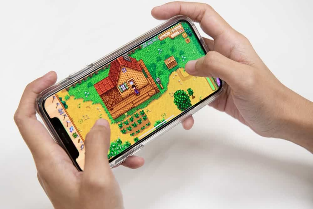 Hands playing a video game on mobile phone.
