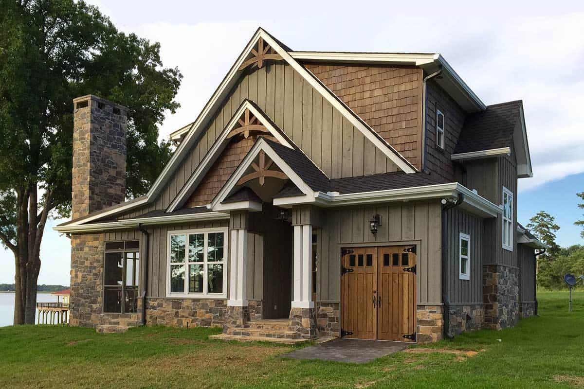 A quaint and charming lakeside cottage with wooden A-frame roofs paired with wooden shiplap walls and stone base to match the stone chimney adorned with a tall tree.