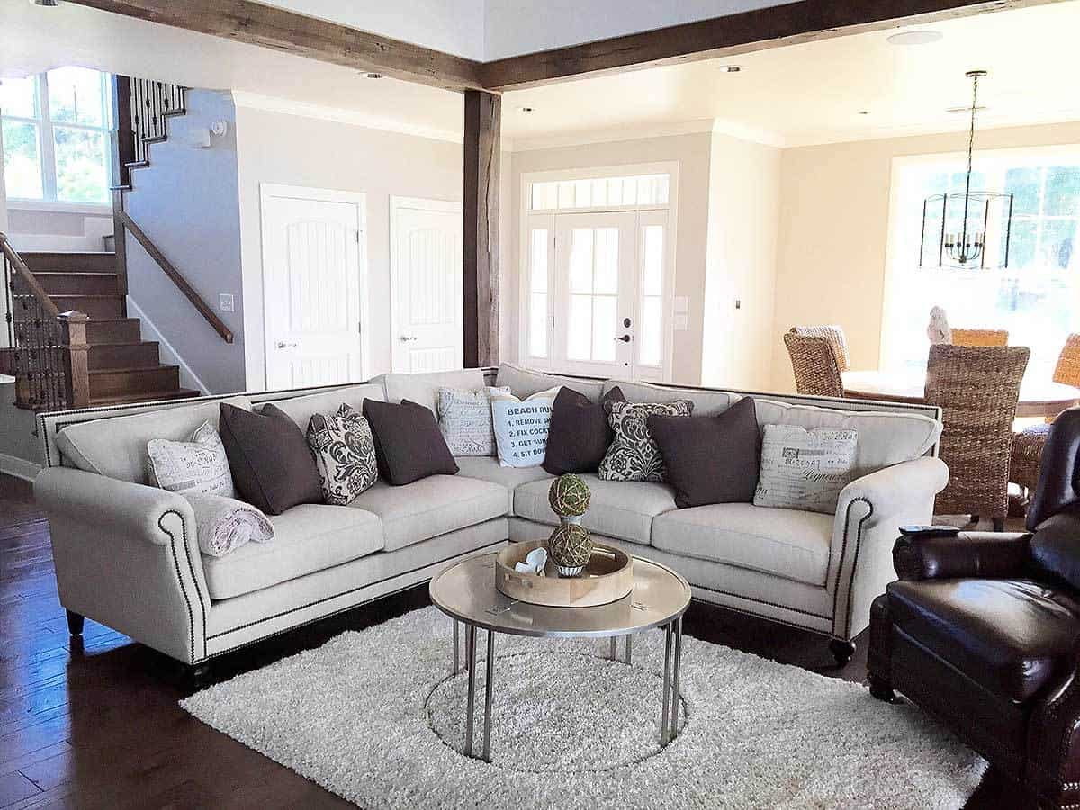 The charming living room of the cottage has a dark hardwood flooring that pairs with the pillows of the L-shaped sofa as well as the dark brown leather arm chair beside it.