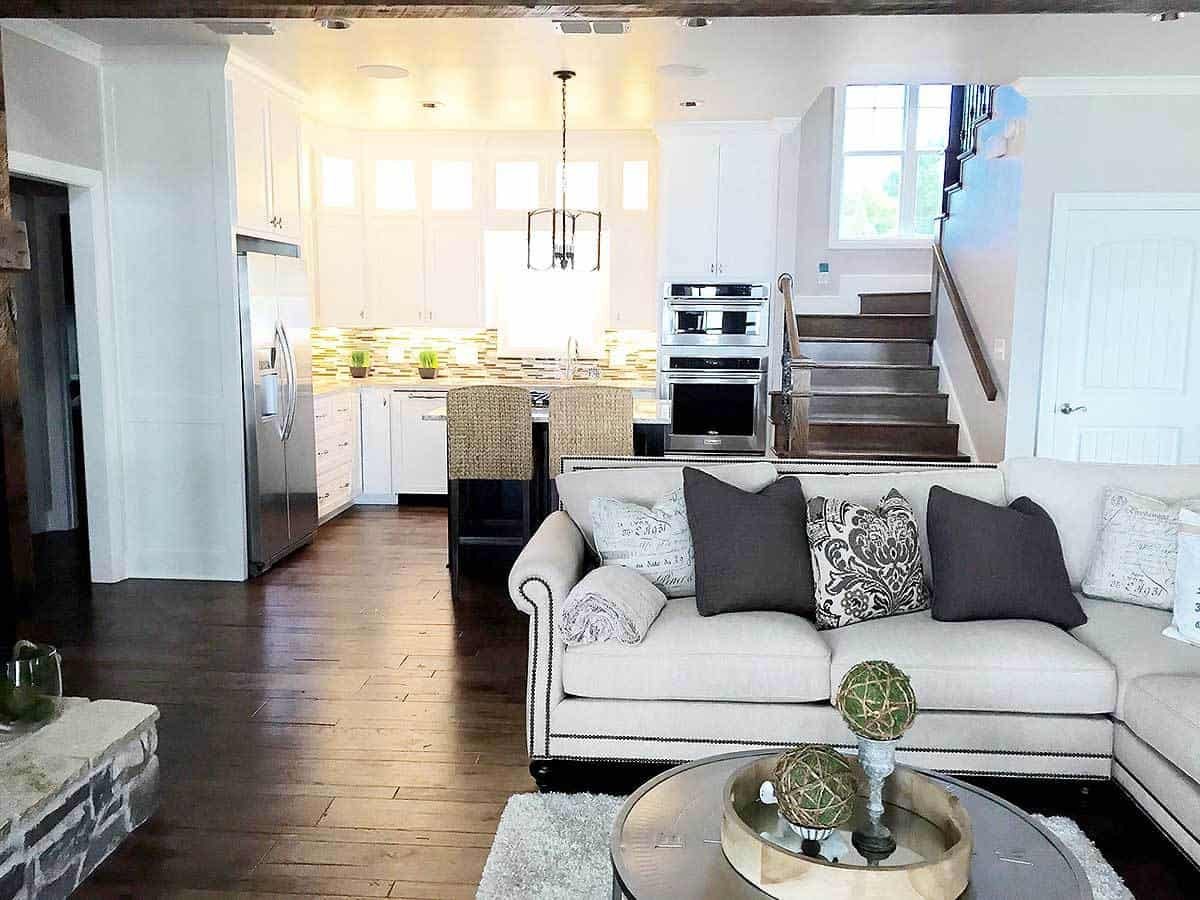 Beside this large L-shaped sofa is the kitchen by the staircase. It has the same dark hardwood flooring and white ceiling. This vantage makes the stainless steel appliances stand out in the kitchen.