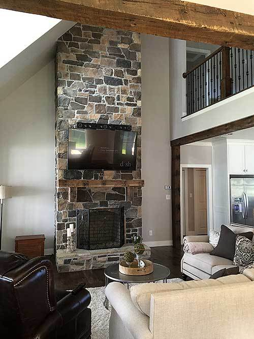 This tall stone pillar reaches all the way to the high ceiling of the living room that has a nice view of the second floor indoor balcony that has wooden banisters and wrought iron railings.