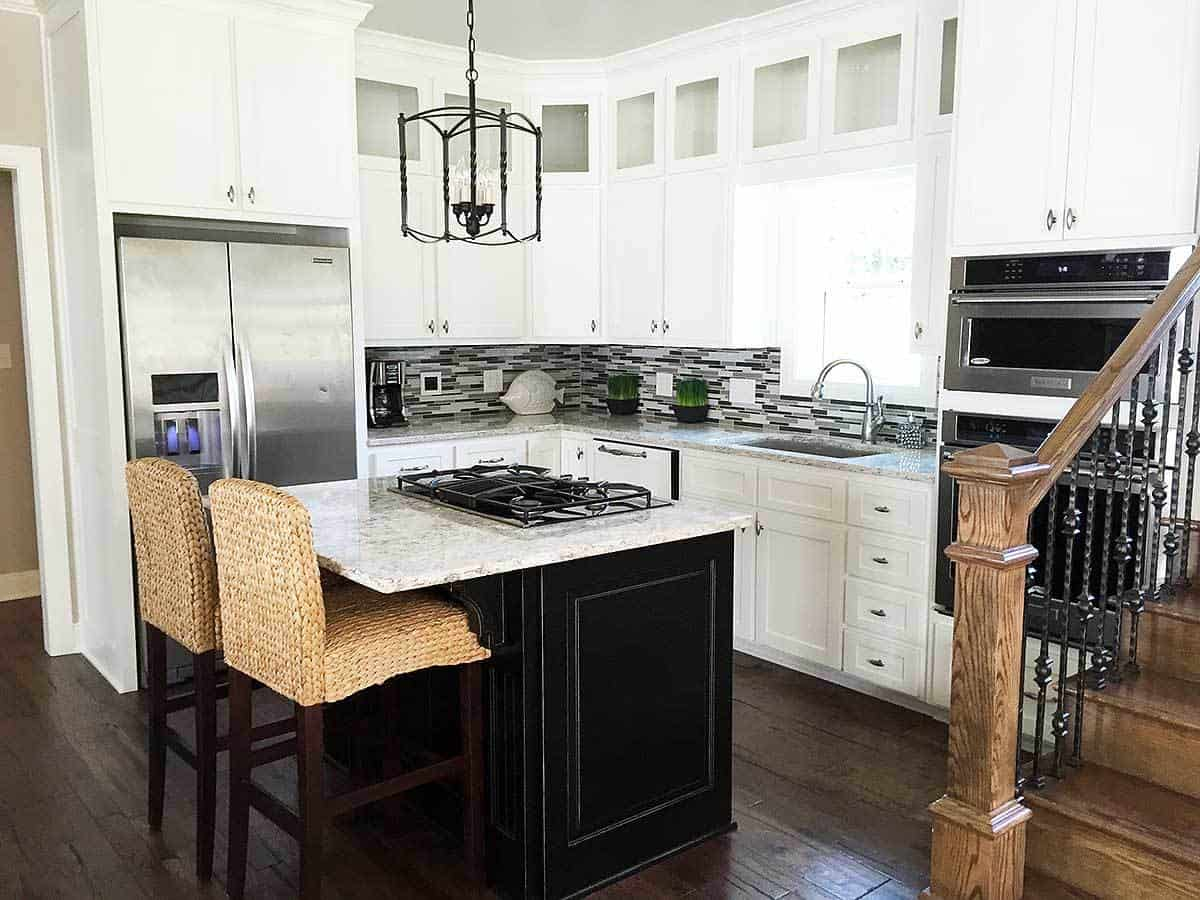 A closer look at the kitchen shows its small kitchen island and breakfast bar with a couple of woven wicker stools to pair with the black island contrasted by the white marble countertop.
