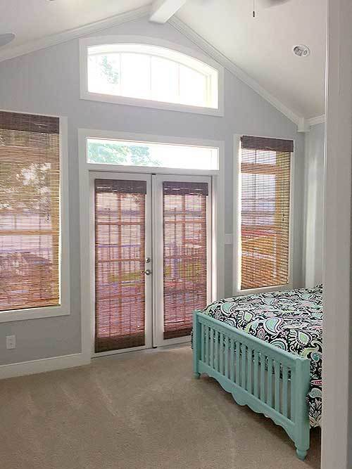 One of the rooms of the cottage has a cathedral ceiling complemented by the simple light gray walls. These are all brightened by the transom window of the glass doors that are dimmed with shades.