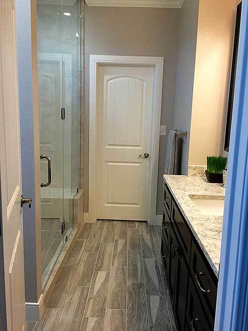 This bathroom has a dark brown vanity contrasted by the light marble countertop. Across from this is the glass door of the walk-in shower.