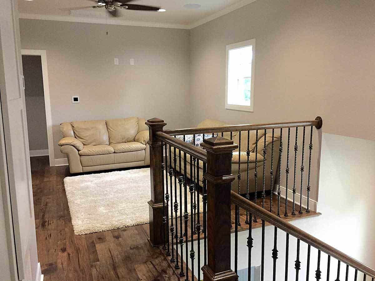 The second floor hallway has its own living room area with a couple of beige leather sofas placed against the walls paired with a furry area rug on the dark hardwood flooring.