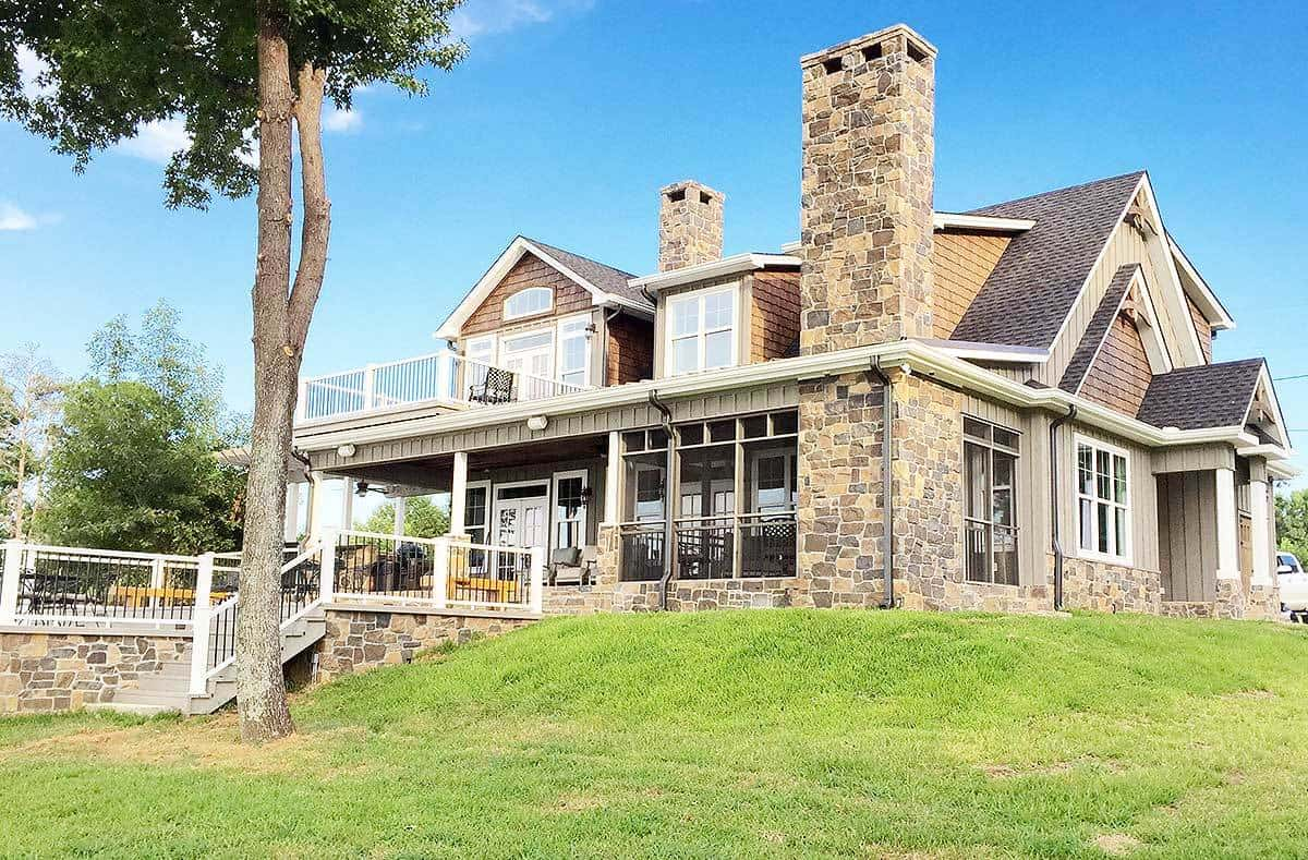 This view from the side of the charming home highlights the tall stone chimneys that tower over the gray roofs of the cottage. There is also a large backyard patio beneath the small balcony of the second floor.