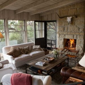 Formal living room featuring a white sofa set along with a brown leather couch, a center table and a fireplace. Images courtesy of Toptenrealestatedeals.com.
