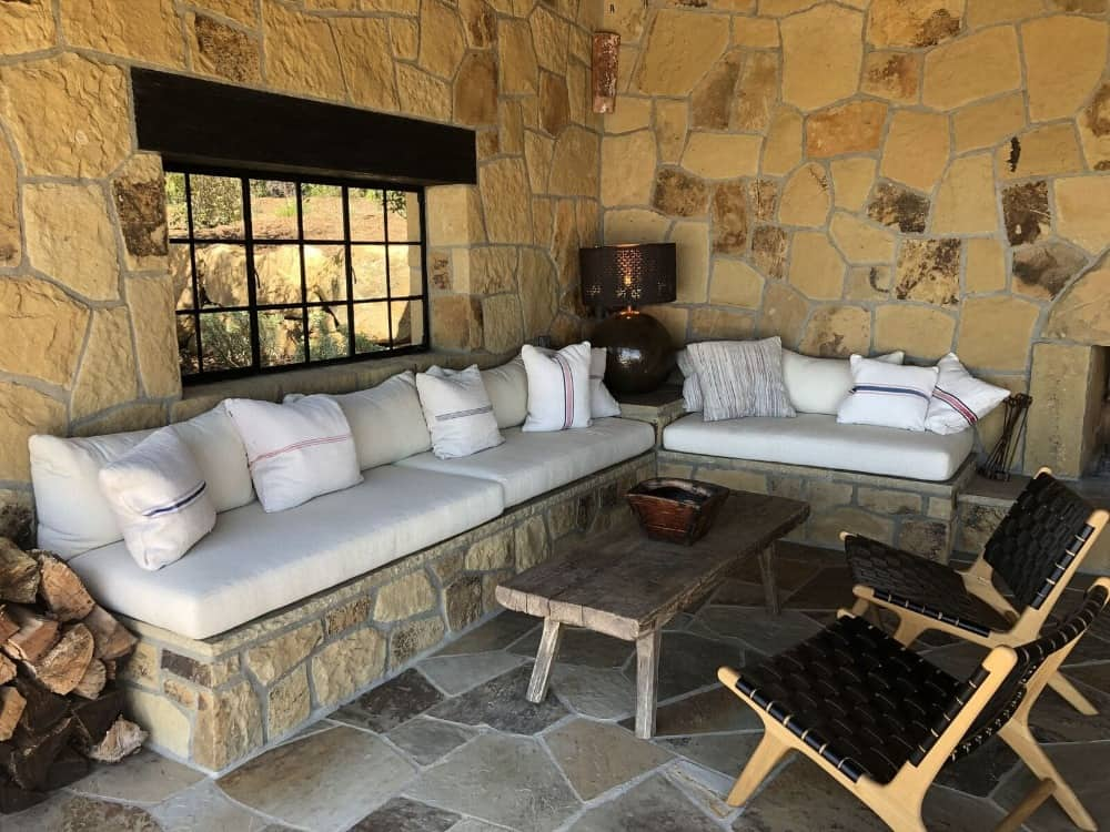 This outdoor living offers a stone bench seating with cushion seats lighted by a table lamp in the corner. Images courtesy of Toptenrealestatedeals.com.