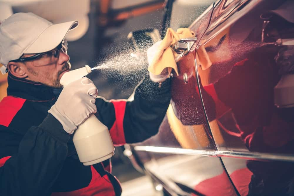 A man doing detailing and maintenance on a red car.