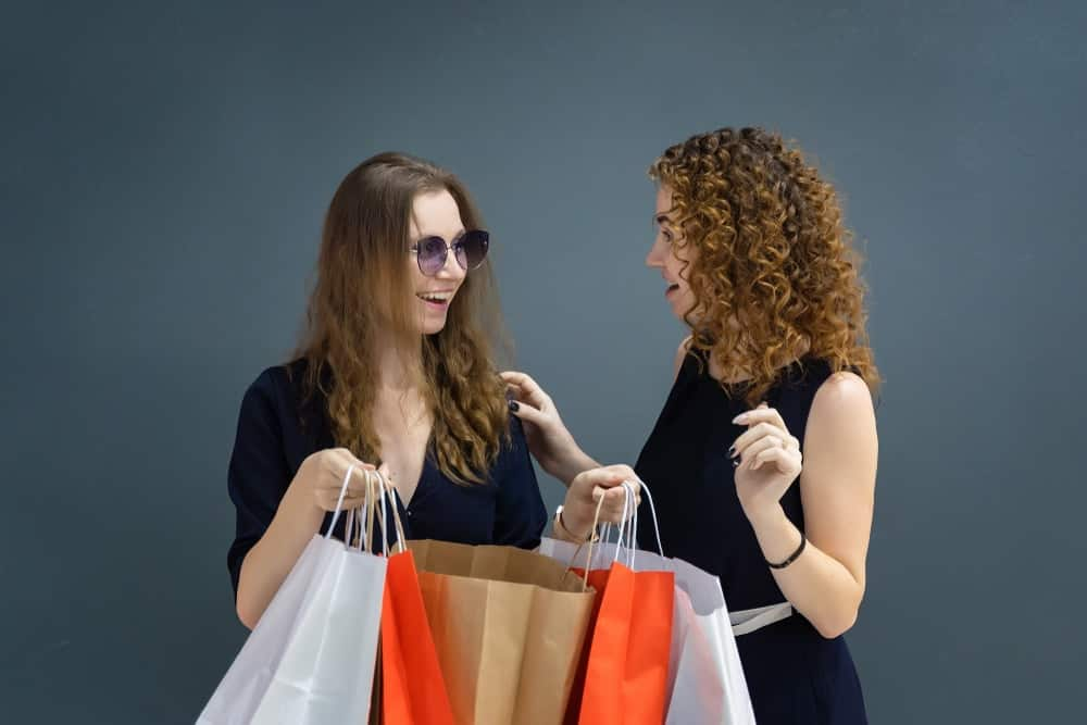 A woman showing her friend what she bought.