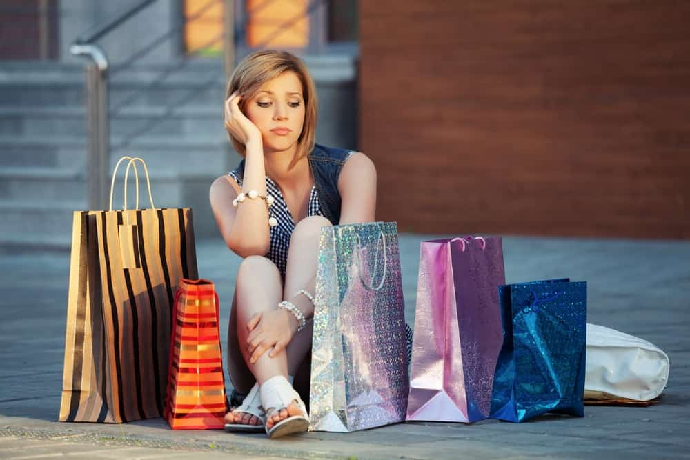 A young woman sad about her recent purchases.