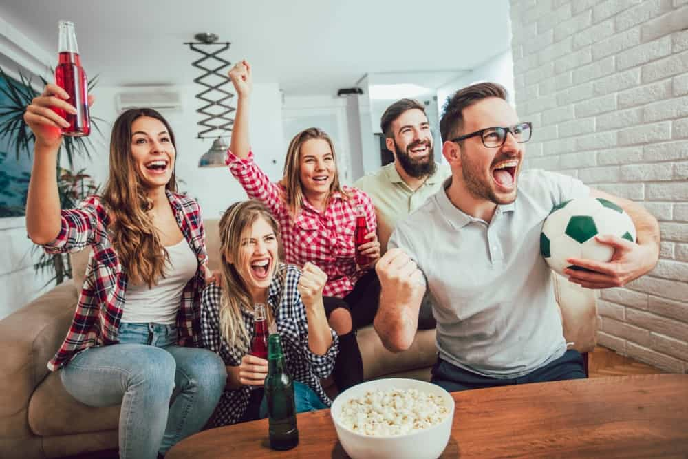 A group of friends watching a game on TV together.