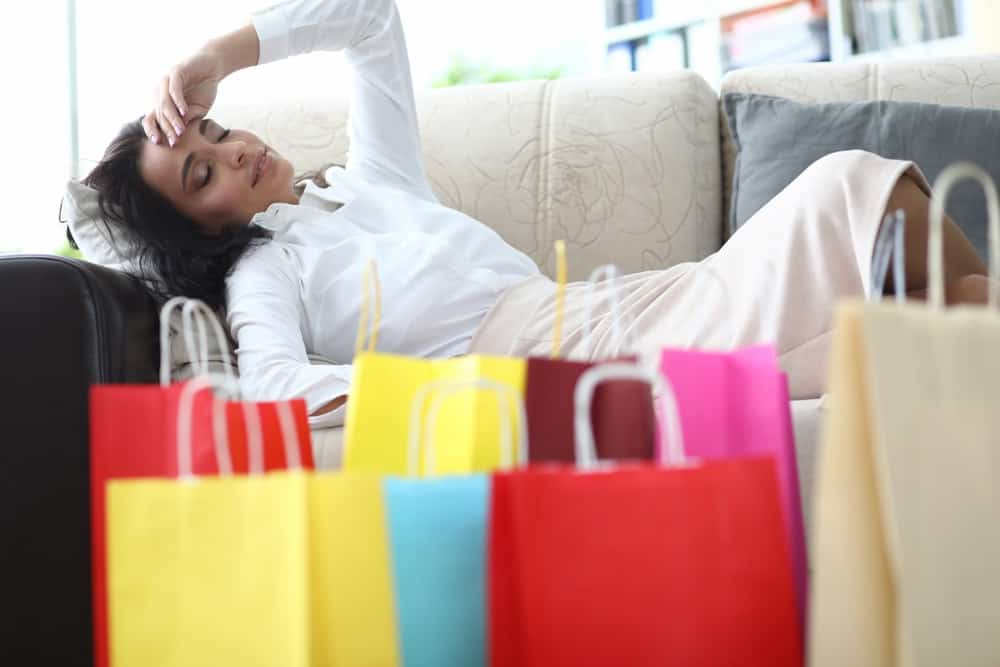 A woman tired on the couch after shopping.