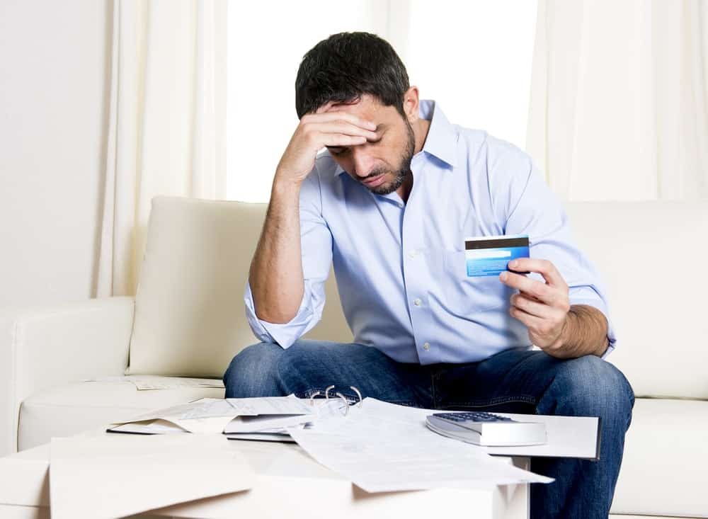 A man worrying about his credit card debt problems.