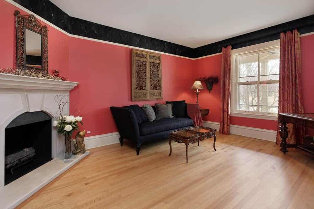 A living room with red walls, black couch, a fireplace with ornate mirror on top and a white framed window covered in patterned drapes.