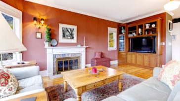 A beautiful family room with an earthy red tone to its walls to pair with the wooden details of the floor and coffee table.