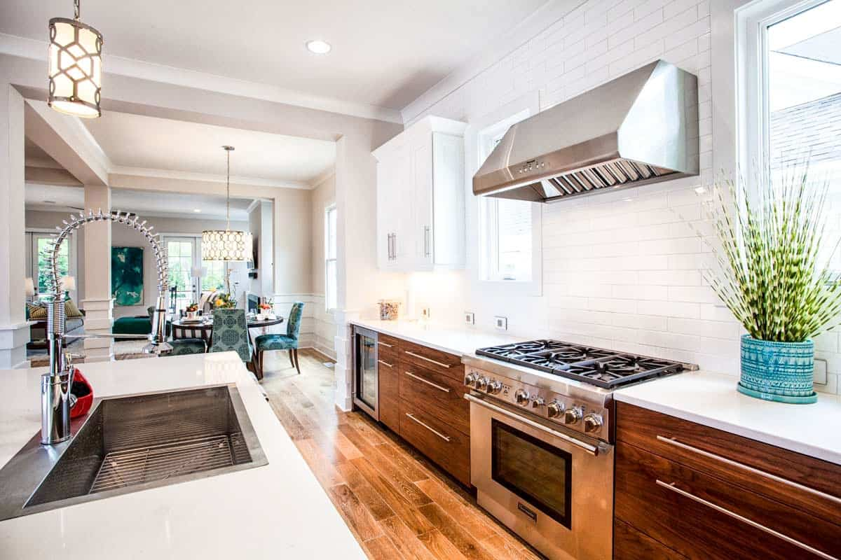 The home's kitchen has a galley layout. It showcases natural wood cabinets and a quartz top island fitted with an undermount sink.