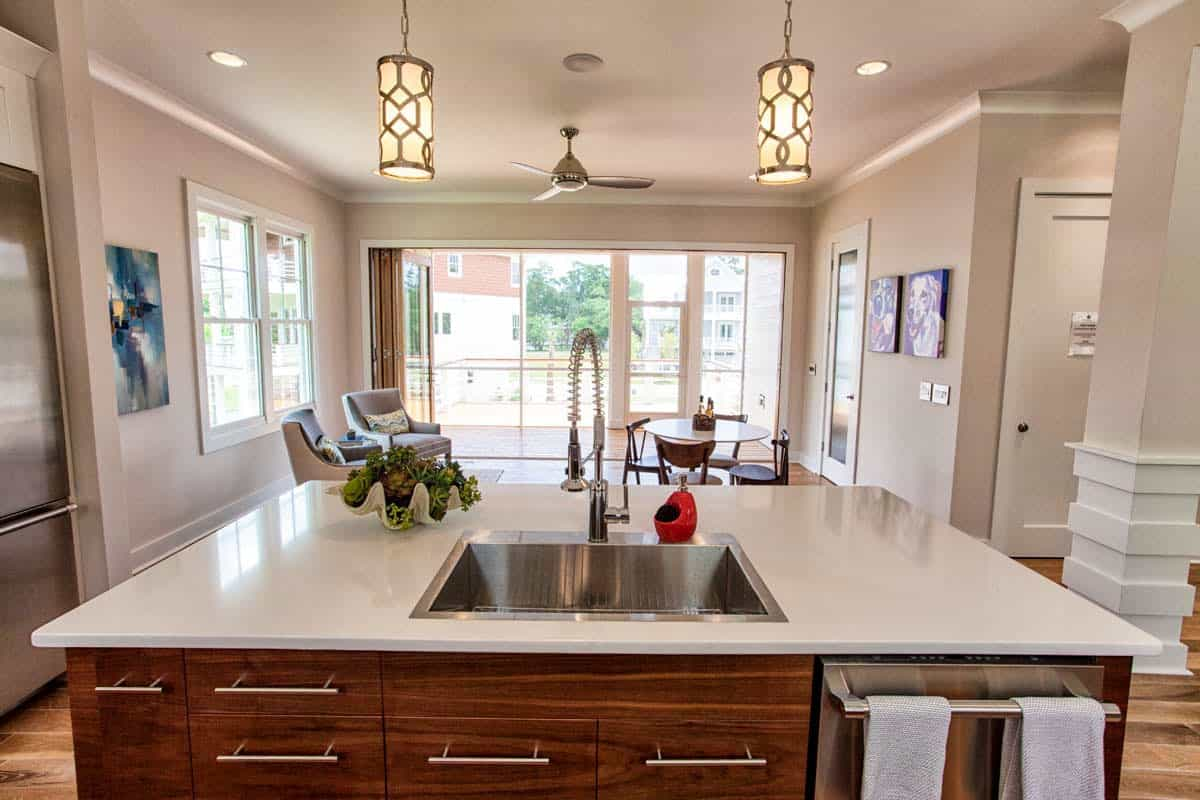 The kitchen island faces the breakfast nook that's situated across the sitting area. It is well-lit by a pair of cylindrical pendants.