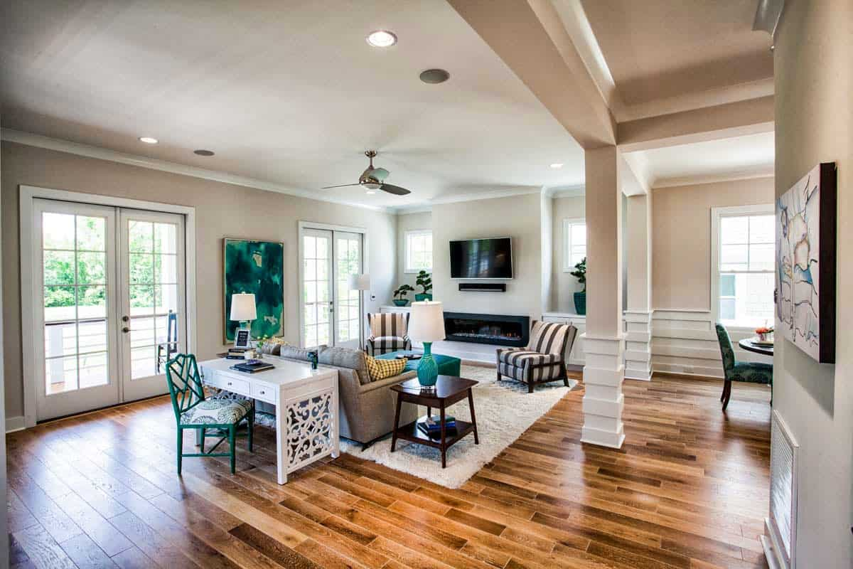 The spacious living area is filled with cozy seats, a modern fireplace under the TV, and an ornate white desk sitting behind the sofa. There are french doors on the side leading out to the porch.