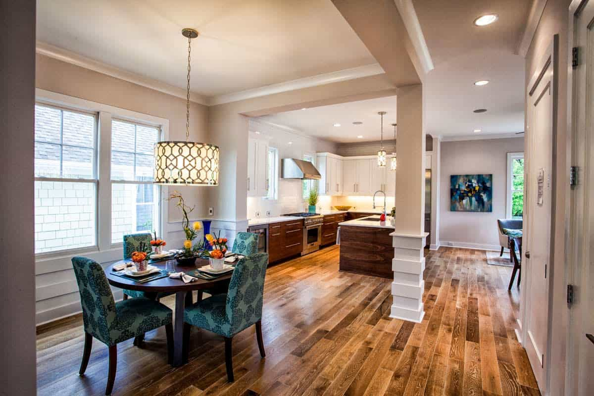 Across the kitchen is the dining area. It showcases patterned upholstered chairs and a round dining table illuminated by a drum chandelier.