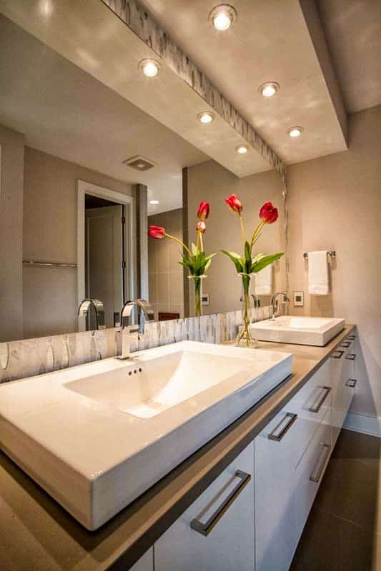 The bathroom features a sleek vanity topped with dual vessel sinks. A large mirror on top creates a sense of space.