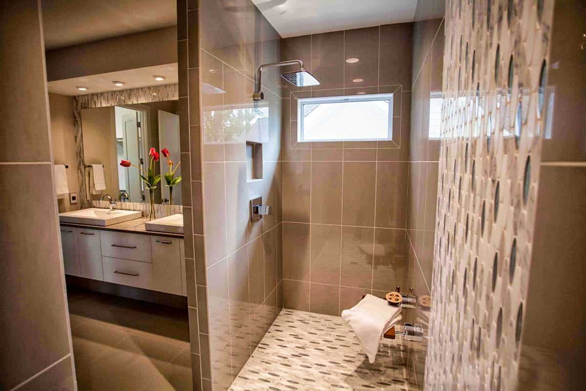 Next to the vanity is the walk-in shower. It has chrome fixtures and a rectangular window that lets natural light in.