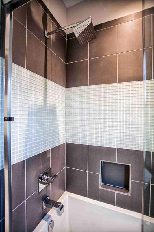 A closer view at the second bathroom shows a shower and tub combo fixed against the taupe tiled walls. Gray mosaic tiles provide a sleek contrast.