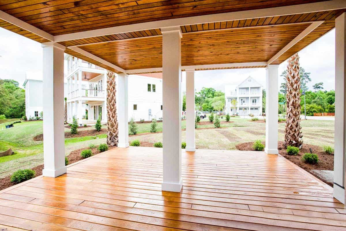 The spacious porch overlooks the garden. It is framed with white columns that are sandwiched by wide plank flooring and a matching ceiling.