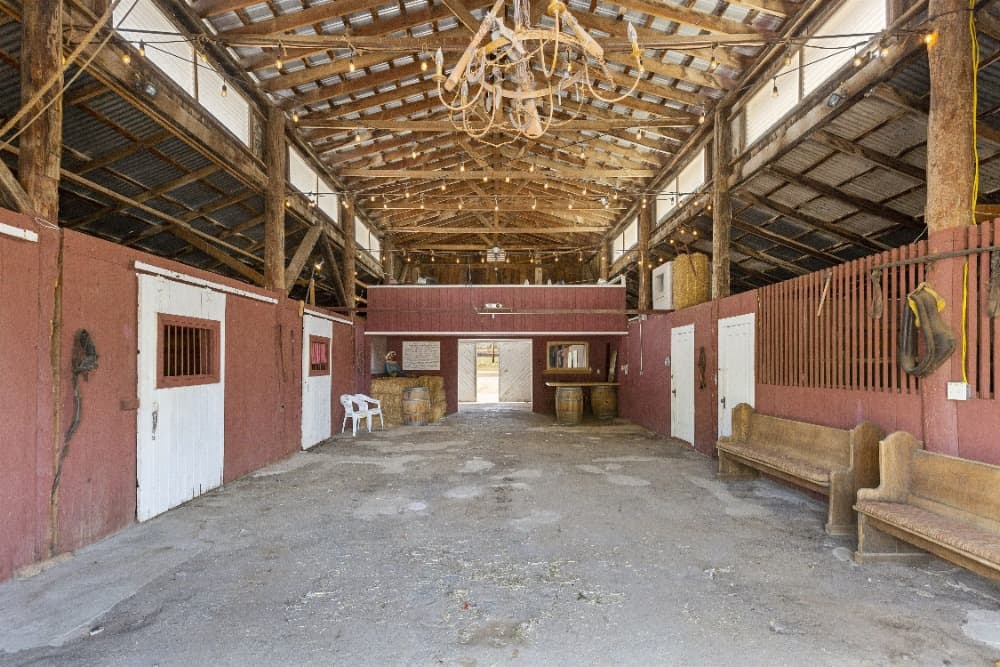 Here's the stable's interior featuring a pair of bench seating and a high ceiling with exposed beams. Images courtesy of Toptenrealestatedeals.com.