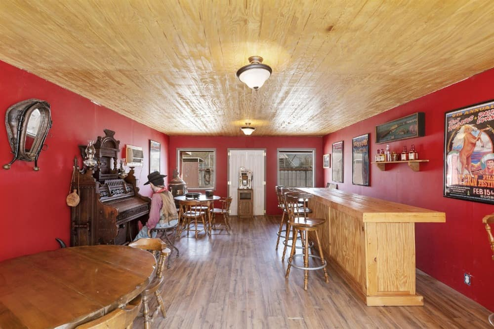 The bar features hardwood floors, red walls and a wooden ceiling, along with round tables and a bar area. Images courtesy of Toptenrealestatedeals.com.