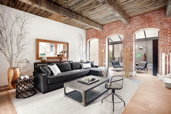 This rustic living room has a dynamic red brick wall that has arched entryways that bring in natural lighting to the black L-shaped sofa that stands out against the light gray area rug.