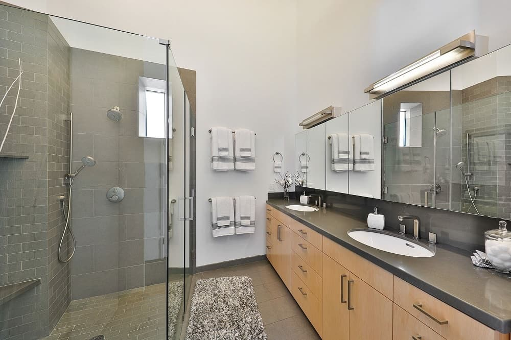 The bathroom has a large two-sink vanity with a black countertop across from the glass-enclosed walk-in shower area. Images courtesy of Toptenrealestatedeals.com.