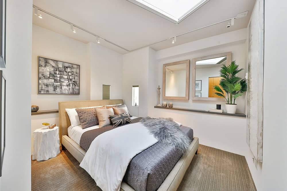 The other bedroom has a carpeted flooring that matches well with the beige cushioned frame of the bed as well as the beige walls brightened by a sun roof. Images courtesy of Toptenrealestatedeals.com.