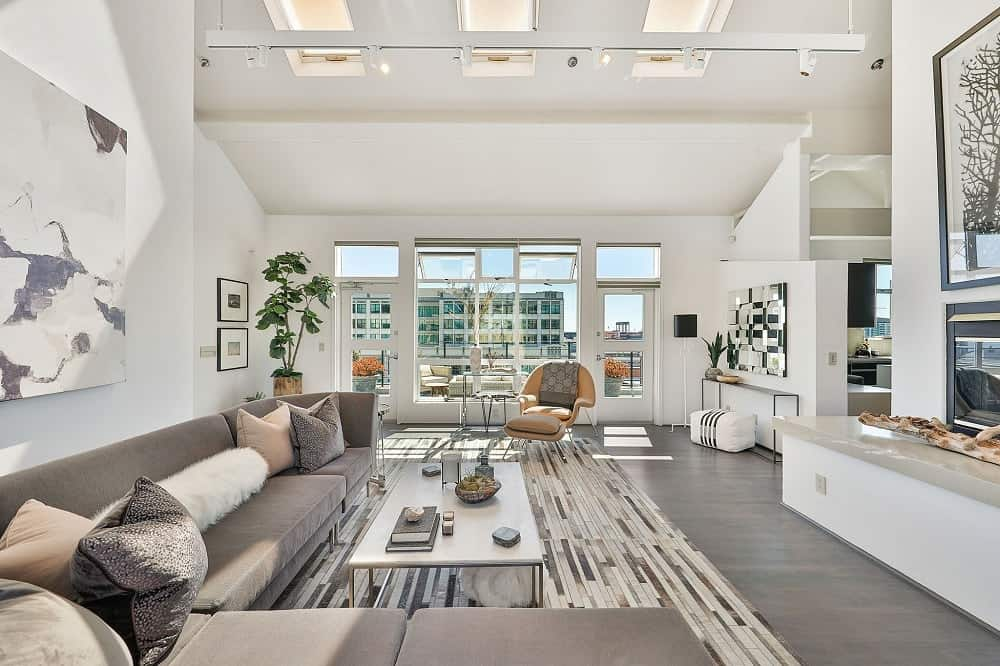 The dark gray L-shaped sofa lines the white walls that are brightened by the glass windows and doors on both sides. Images courtesy of Toptenrealestatedeals.com.