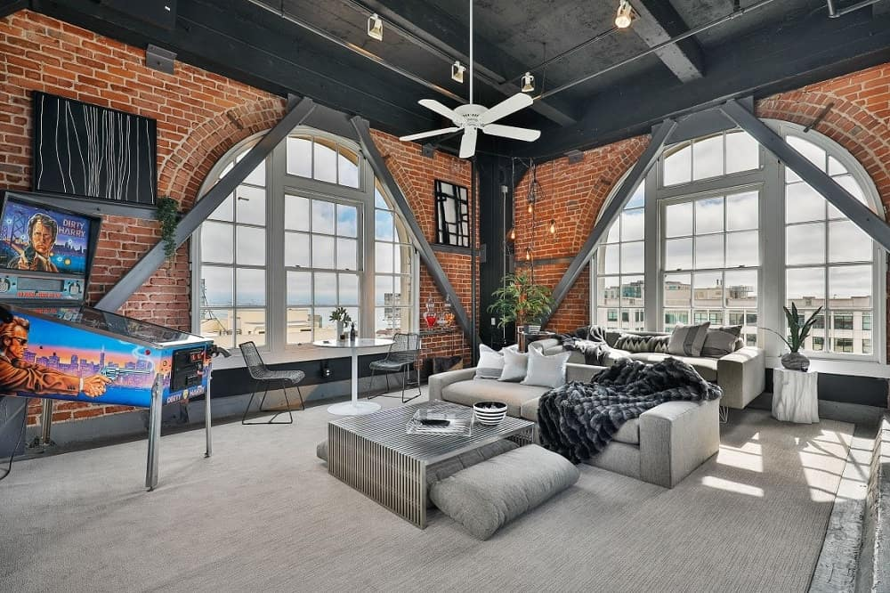 This spacious and airy living room has red brick walls that go well with the black ceiling and the exposed beams. These are then complemented by the large arched windows.
